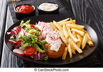 Delicious lunch of roasted pollock breaded with french fries and fresh salad close-up on a plate and sauces. horizontal
