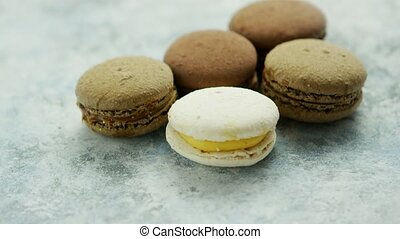 Closeup of white and chocolate macarons with different fillings composed in small heap on marble surface
