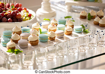 delicious macaroons and cupcakes on table at wedding reception. candy bar. tasty colorful sweets for celebrations events and showers. luxury stylish catering