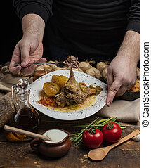 delicious meat meal with garlic on dark background