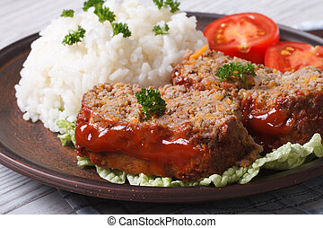 meatloaf with rice and tomatoes on a plate close-up