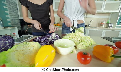 Delicious mess in the kitchen. Young smiling friends cook ...