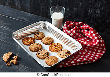 Delicious natural oatmeal cookies baked - chocolate, nut, with raisins on a baking sheet with a glass of milk and a red towel on a black wooden table.