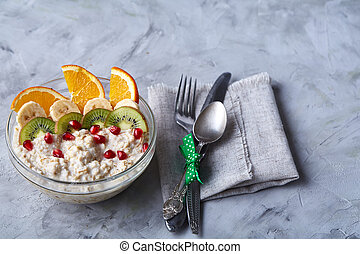 Delicious oatmeal with fruits in glass bowl isolated on white textured background, copy space, selective focus