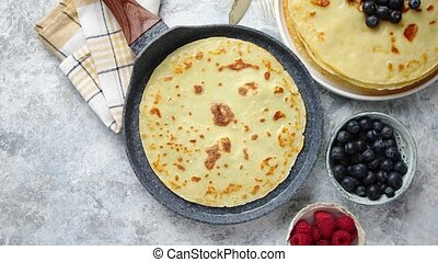 Delicious pancakes on stone frying pan. Placed on table with...