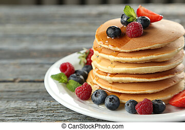 Delicious pancakes with berries on blue wooden background