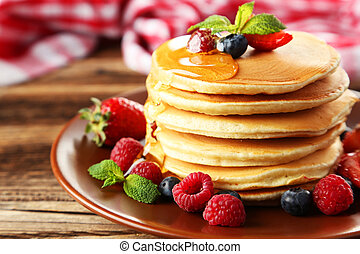 Delicious pancakes with berries on brown wooden background