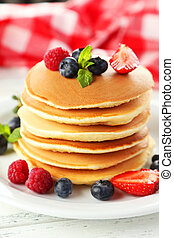Delicious pancakes with berries on white wooden background