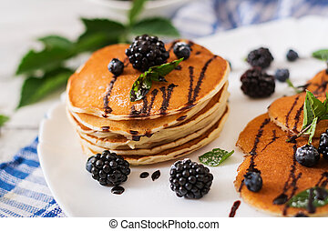 Delicious pancakes with blackberries and chocolate.