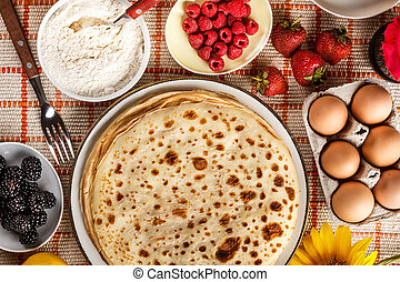 Delicious pancakes with fruit on the kitchen table