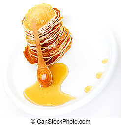 Delicious pancakes with honey syrup over white plate