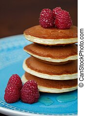 Delicious pancakes with raspberries and honey in a bowl