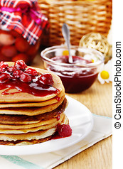 Delicious pancakes with raspberries on the wooden kitchen...