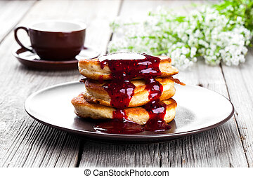 Delicious pancakes with raspberries sauce on the wooden kitchen