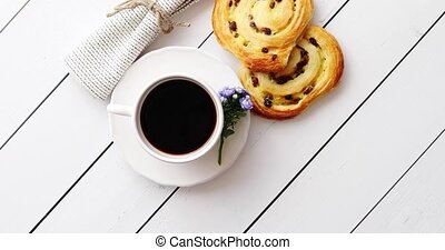 Delicious pastry with raisins and a cup of coffee top view....