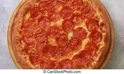 Delicious pepperoni pizza spinning on the table. top view on...
