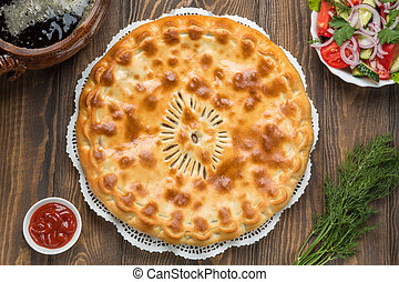 Delicious pie on the table next to the vegetables