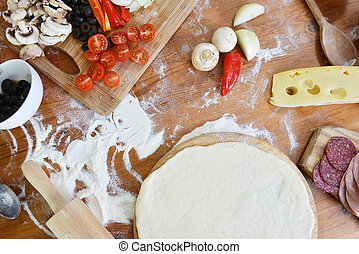 delicious pizza dough, spices and vegetables on wooden table