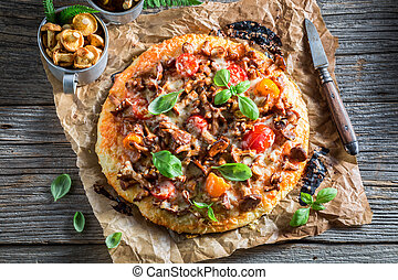 Delicious pizza made of noble mushrooms and tomatoes