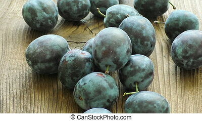 Delicious plums on the old wooden background
