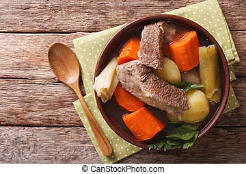 Delicious Pot-au-feu beef soup with vegetables close up in a...