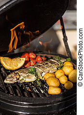 Delicious rainbow trout fish with tomatoes, potatoes and lemon cooking on hot flaming grill. Barbecue. Restaurant