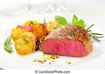 Cut through portion of delicious bloody rare to medium rare fillet steak served with crispy roasted potatoes, fresh rosemary and rocket on a white plate