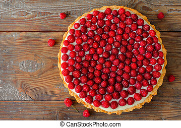Delicious raspberry tart on a wooden board