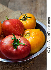 Delicious red and yellow tomatoes in a bowl