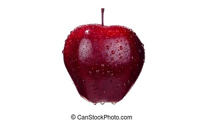 Delicious fresh bright red apple with stem covered with shiny clear water drops turns left side slowly on white background