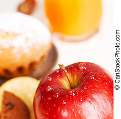 Delicious red apple with baked goods on background