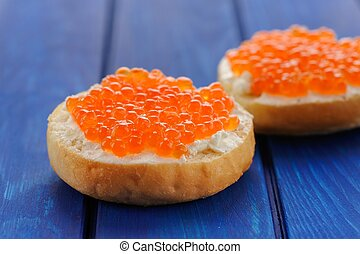 Delicious red caviar on buns with cream cheese on deep blue table