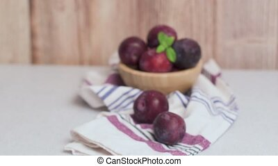 Delicious red plums in a wooden bowl on kitchen countertop.