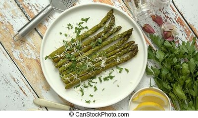 Delicious roasted asparagus served on white ceramic plate. ...
