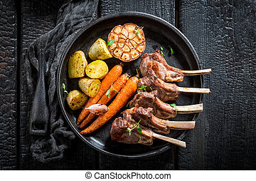 Delicious roasted lamb ribs with thyme on dark background