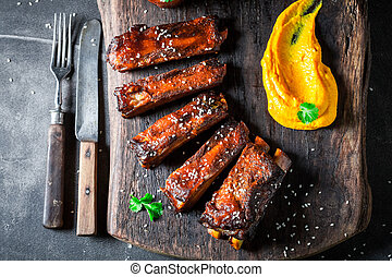 Delicious roasted ribs with vegetables and potato on dark table
