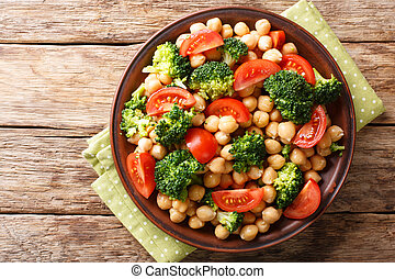 Delicious salad of broccoli, chickpeas and tomatoes closeup on a plate. horizontal top view