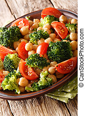 Delicious salad of broccoli, chickpeas and tomatoes closeup on a plate. vertical