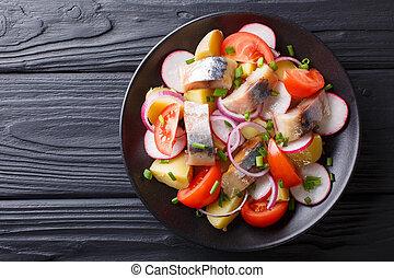 Delicious salad of smoked mackerel with potatoes, radish and tomatoes close-up. horizontal top view