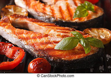 salmon steak and vegetables on the grill, macro. horizontal...