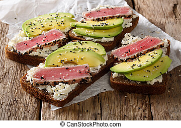 Delicious sandwiches with fried tuna, sesame, avocado and cottage cheese close-up. horizontal