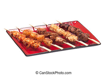 Delicious satay collection on a red plate