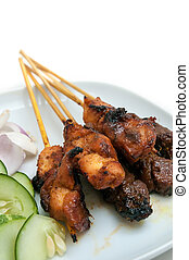Delicious satay with cucumbers and onions served on white plate
