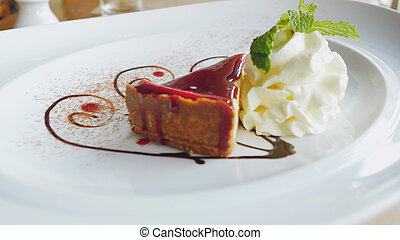 Delicious slice of Cheesecake beautiful served on a white plate with cream and leaf of mint