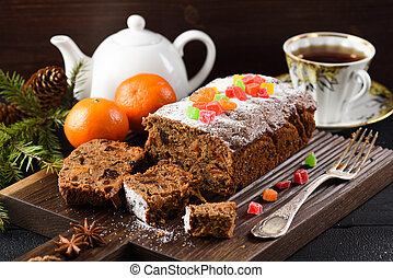Delicious sliced fruit cake on wooden board served with tea and clementines