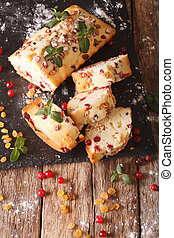 Delicious Sliced fruit cake with cranberries and raisins decorated with mint closeup. vertical