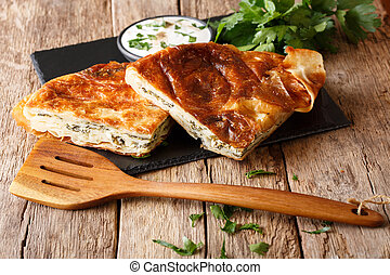 Delicious snack: Balkan burek with spinach and cheese close-up on the table. horizontal