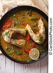 Delicious spicy fish curry with cilantro close up. vertical top view