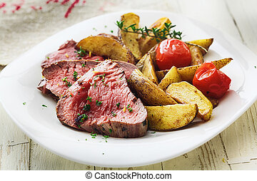 Delicious succulent rare beef steak sliced and served with...