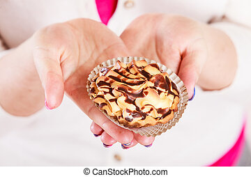 Delicious sweet cupcake in human hand.